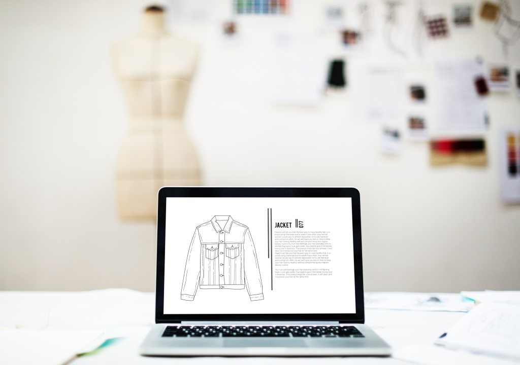 Vector drawing of a denim jacket on a an open laptop with blurred image of a tailors dummy in the back of the room