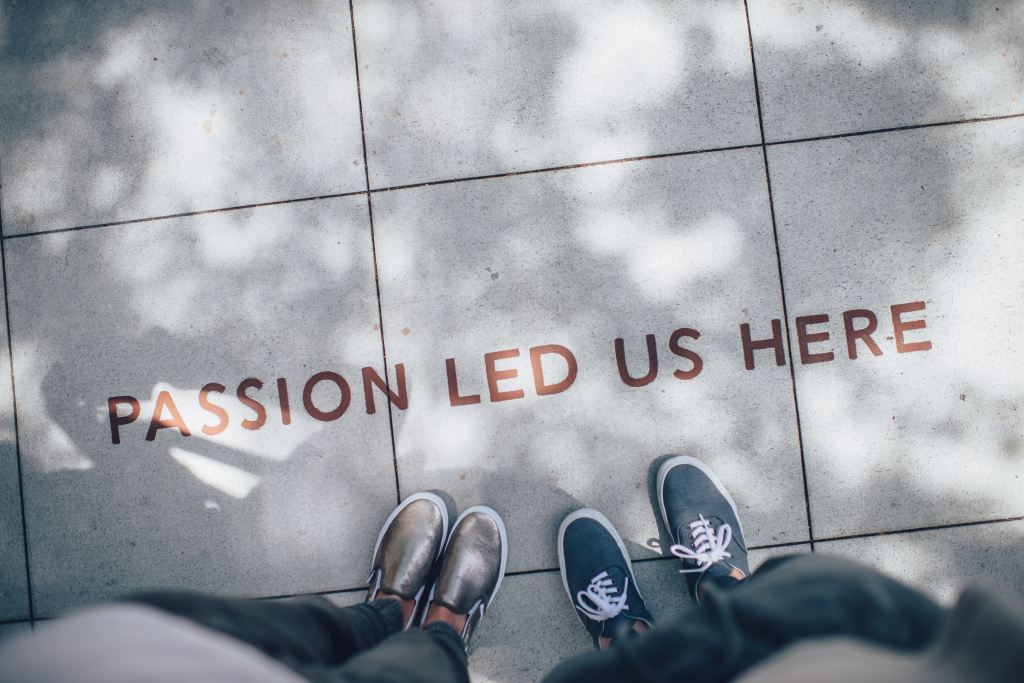 feet on a concrete paved floor with the words 'passion led us here' printed on them