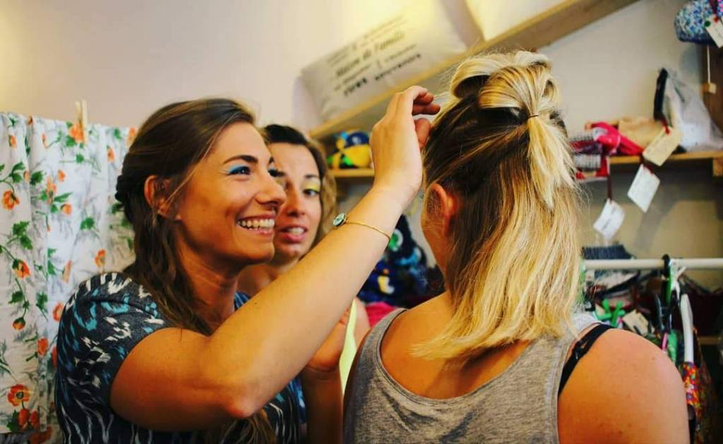 girls fixing each others hair and smiling
