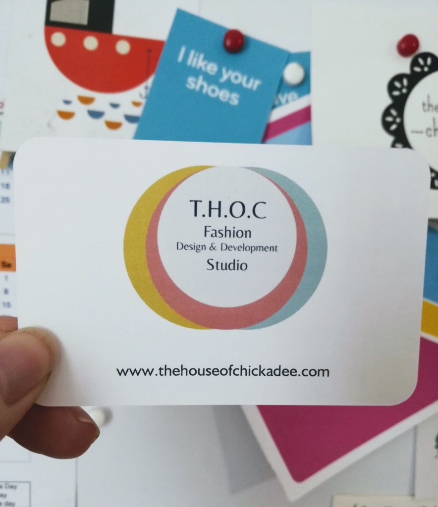 an image of a 'the house of chickadee'/ T.H.O.C. design & development studio, business card being held infront of other colourful cards