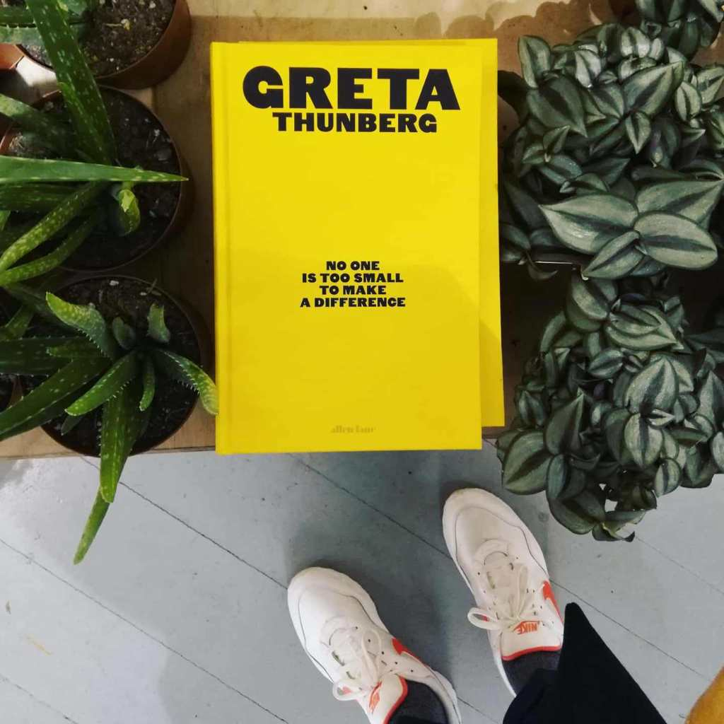 A persons feet standing beside a display of green plants and a bright yellow book entitled 'no one is too small to make a difference' by Greta Thunberg