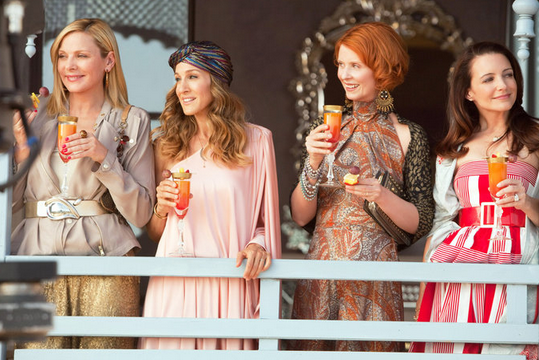 a scene from tv show Sex in the City showing the 4 main characters with drinks in their hands