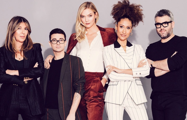 the judges and presenters of Project Runway wearing suits and posing