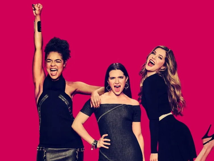 The 3 main characters from The Bold Type wearing little black dresses with their mouths open in a sort of happy cheer